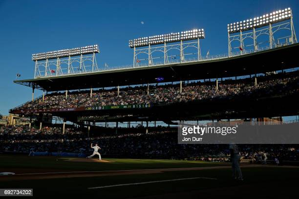 Eddie Butler of the Chicago Cubs pitches against Derek Dietrich of the Miami Marlins during the second inning as the moon begins to rise above...