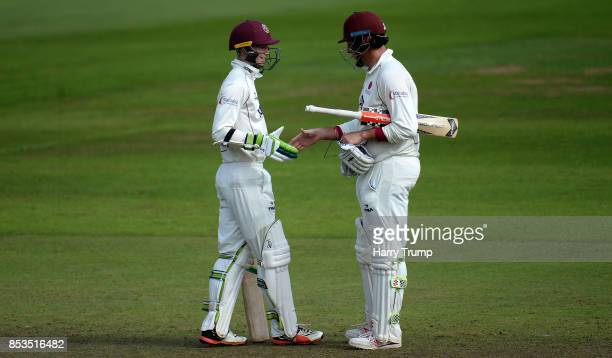 Eddie Byrom of Somerset celebrates his half century with Marcus Trescothick of Somerset during Day One of the Specsavers County Championship Division...