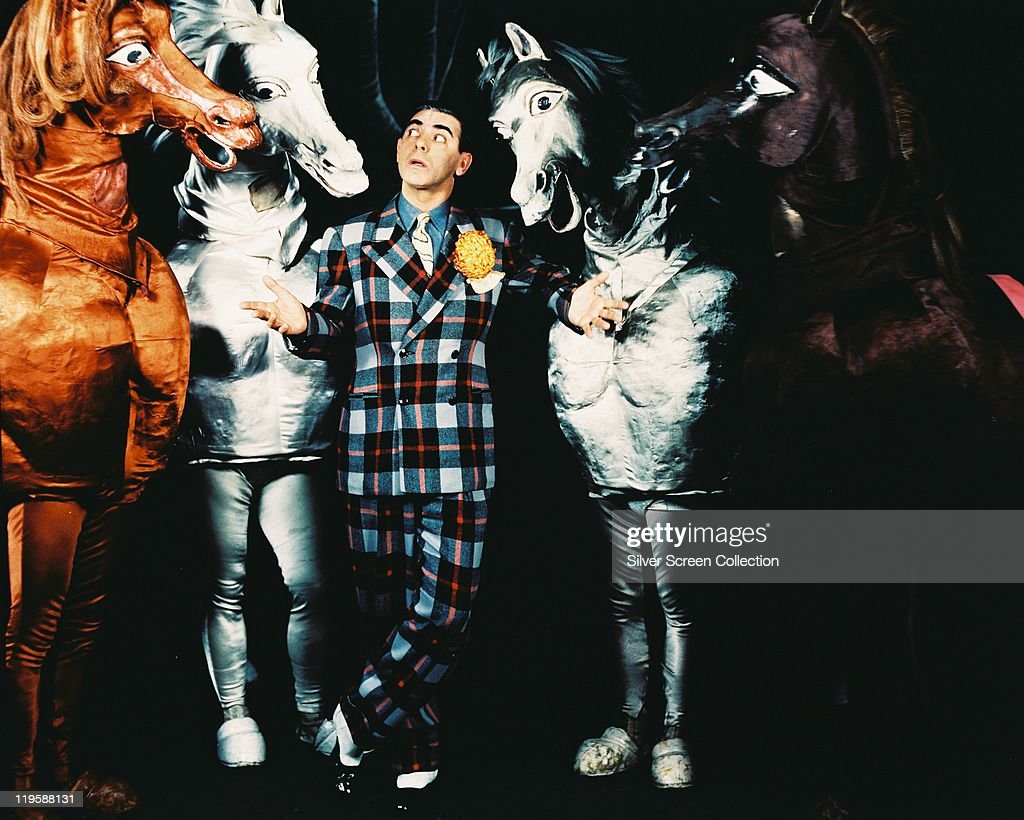 <a gi-track='captionPersonalityLinkClicked' href=/galleries/search?phrase=Eddie+Cantor&family=editorial&specificpeople=93329 ng-click='$event.stopPropagation()'>Eddie Cantor</a> (1892-1964), US actor and comedian, wearing a plaid suit as he poses with four pantomime horses, against a black background, circa 1935.