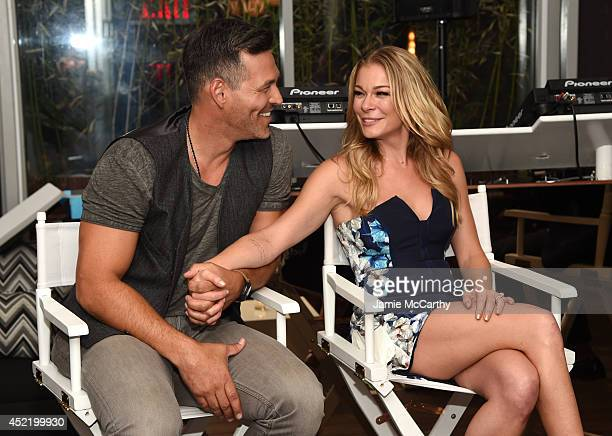 Eddie Cibrian and LeAnn Rimes speak at the LeAnn Eddie Screening Party at Attic Rooftop Lounge on July 15 2014 in New York City