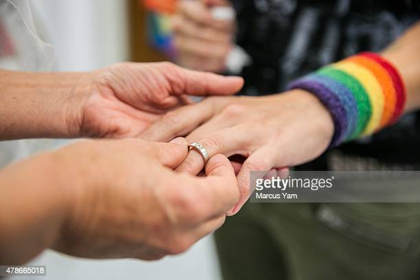Eddie Daniels places a wedding ring on her partner Natalie Novoa's finger during their wedding ceremony at the LA County Registrars office on June 26...