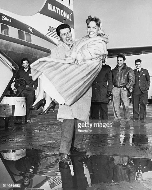 Eddie Fisher carries wife Debbie Reynolds as they disembark their plane at Idlewild Airport The pair arrived to attend the December 19th premiere of...