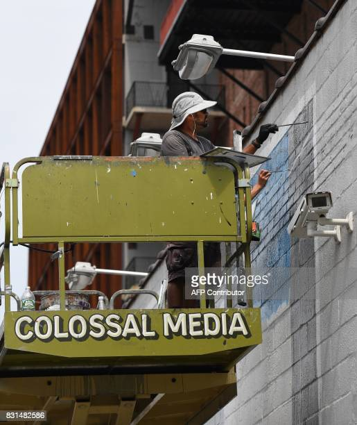 Eddie Garcia a freelance painter for Colossal Media paints an ad on the side of Colossal Media's office building August 2 in New York Colossal Media...