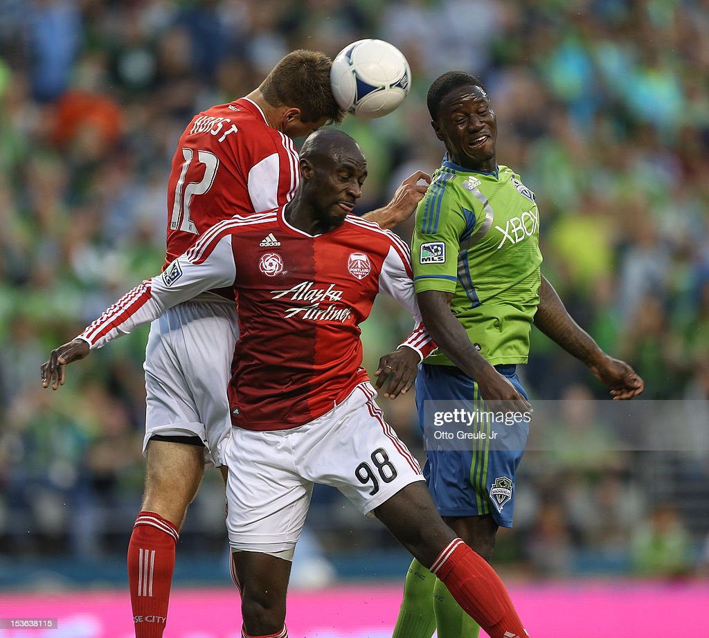Eddie Johnson #7 of the Seattle Sounders FC heads the ball against David Horst #12 and Mamadou 'Futty' Danso #98 of the Portland Timbers at CenturyLink Field on October 7, 2012 in Seattle, Washington.