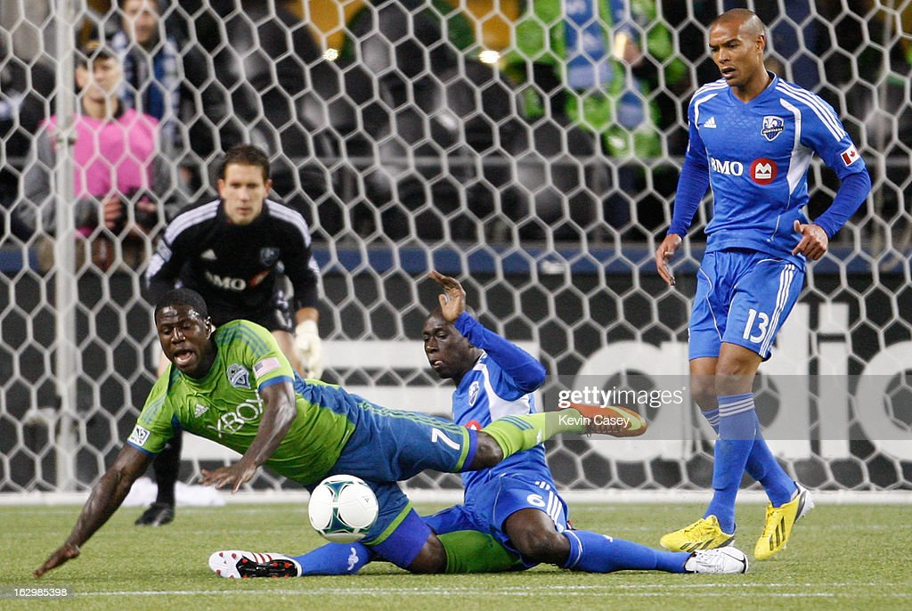 Eddie Johnson #7 of the Seattle Sounders goes to the turf as Hassoun Camara #6 of Montreal Impact slides to stop the ball with goalie Evan Bush #30 and Matteo Ferrari #13 looking on in the first half at CenturyLink Field on March 2, 2013 in Seattle, Washington.