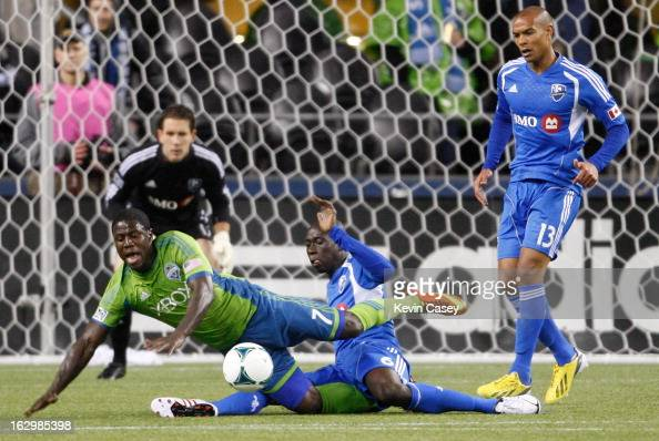 Eddie Johnson of the Seattle Sounders goes to the turf as Hassoun Camara of Montreal Impact slides to stop the ball with goalie Evan Bush and Matteo...