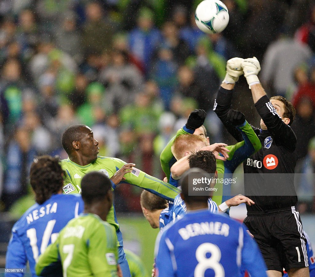 Eddie Johnson #7, (L) of the Seattle Sounders looks on as <a gi-track='captionPersonalityLinkClicked' href=/galleries/search?phrase=Troy+Perkins&family=editorial&specificpeople=596206 ng-click='$event.stopPropagation()'>Troy Perkins</a> #1, goalie of Montreal Impact punches the ball away in the second half at CenturyLink Field on March 2, 2013 in Seattle, Washington.