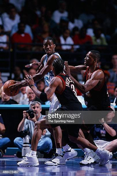 Eddie Jones of the Charlotte Hornets looks to pass over Allen Iverson and Theo Ratliff of the Philadelphia 76ers during the game on May 4 1999 at...