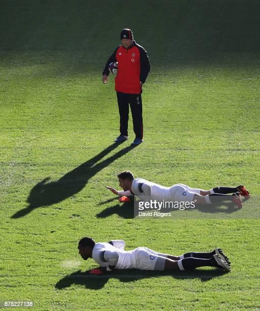 Eddie Jones the England head coach looks on as Semesa Rokoduguni and Danny Care warm up during the England captain's run at Twickenham Stadium on...