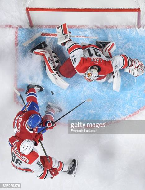 Eddie Lack and Teuvo Teravainen of the Carolina Hurricanes defend the goal against Artturi Lehkonen of the Montreal Canadiens in the NHL game at the...