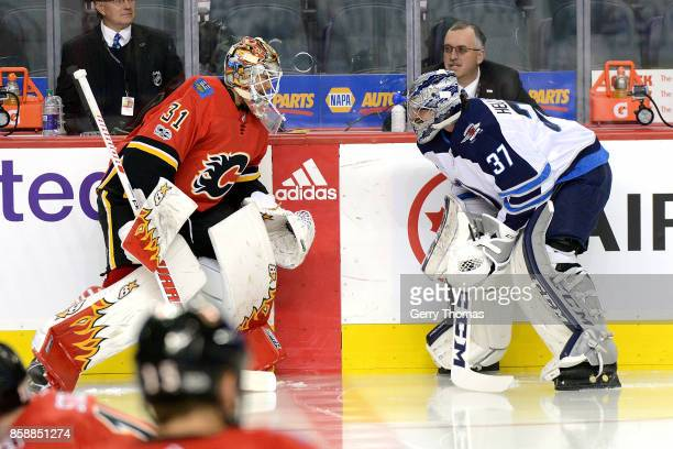 Eddie Lack of the Calgary Flames talks to Connor Hellebuyck of the Winnipeg Jets during an NHL game on October 7 2017 at the Scotiabank Saddledome in...