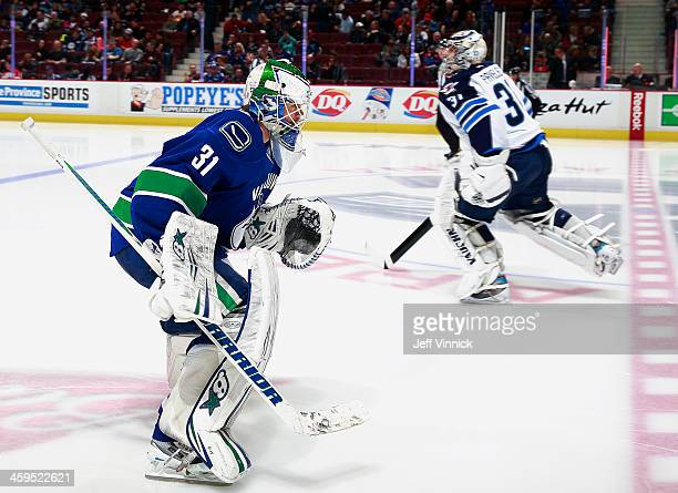 Eddie Lack of the Vancouver Canucks and Ondrej Pavelec of the Winnipeg Jets pass each other on the ice during their NHL game at Rogers Arena December...