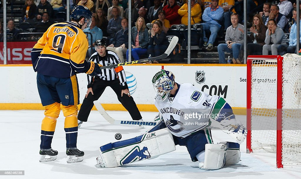 Eddie Lack #31 of the Vancouver Canucks blocks the shot of Filip Forsberg #9 of the Nashville Predators during a shootout at Bridgestone Arena on March 31, 2015 in Nashville, Tennessee.