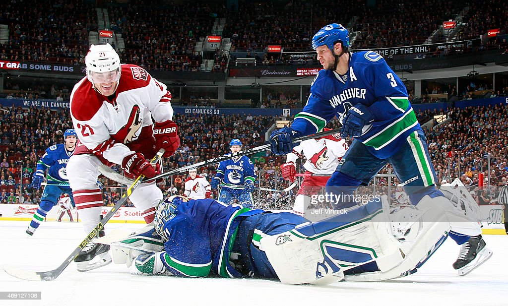 Eddie Lack #31 of the Vancouver Canucks dives to smother the puck on the stick of Jordan Szwarz #21 of the Phoenix Coyotes with Kevin Bieksa #3 of the Canucks watching during their NHL game at Rogers Arena April 9, 2015 in Vancouver, British Columbia, Canada. Vancouver won 5-0.