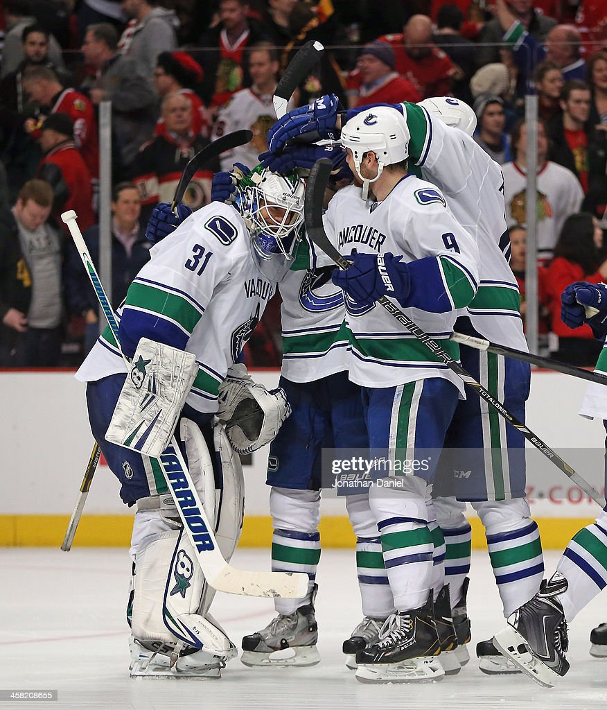 Eddie Lack #31 of the Vancouver Canucks is mobbed by teammates including <a gi-track='captionPersonalityLinkClicked' href=/galleries/search?phrase=Zack+Kassian&family=editorial&specificpeople=4604939 ng-click='$event.stopPropagation()'>Zack Kassian</a> #9 after a win over the Chicago Blackhawks at the United Center on December 20, 2013 in Chicago, Illinois. The Canucks defeated the Blackhawks 3-2 in a shootout.
