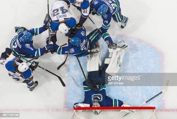 Eddie Lack of the Vancouver Canucks is surrounded by players as he makes a save against the St Louis Blues during their NHL game at Rogers Arena...