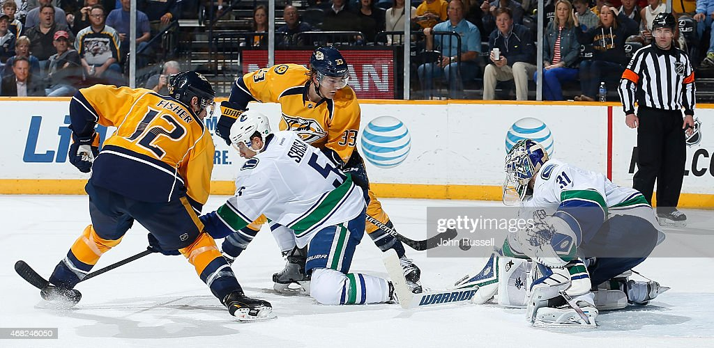 Eddie Lack #31 of the Vancouver Canucks makes the save against Colin Wilson #33 of the Nashville Predators as Canucks Luca Sbisa #5 defends against Predators Mike Fisher #12 during an NHL game at Bridgestone Arena on March 31, 2015 in Nashville, Tennessee.