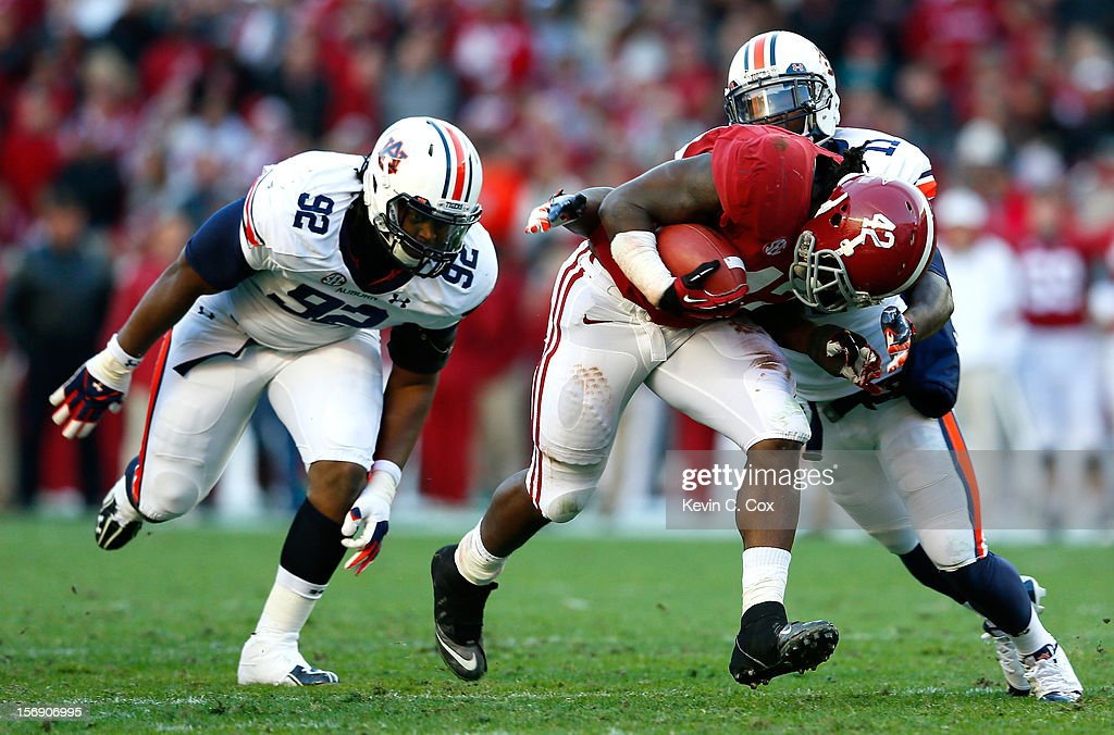 Eddie Lacy #42 of the Alabama Crimson Tide drives against Kenneth Carter #92 and <a gi-track='captionPersonalityLinkClicked' href=/galleries/search?phrase=Chris+Davis+-+American+Football+Cornerback&family=editorial&specificpeople=15200244 ng-click='$event.stopPropagation()'>Chris Davis</a> #11 of the Auburn Tigers at Bryant-Denny Stadium on November 24, 2012 in Tuscaloosa, Alabama.