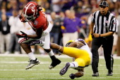 Eddie Lacy of the Alabama Crimson Tide runs with the ball against Brandon Taylor of the Louisiana State University Tigers during the 2012 Allstate...