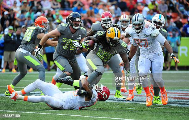 Eddie Lacy of the Green Bay Packers and Team Sanders is tackled by Derrick Johnson of the Kansas City Chiefs and Team Rice during the 2014 Pro Bowl...