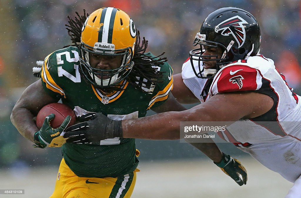 Eddie Lacy of the Green Bay Packers is grabbed on a run by Corey Peters of the Atlanta Falcons at Lambeau Field on December 8 2013 in Green Bay...