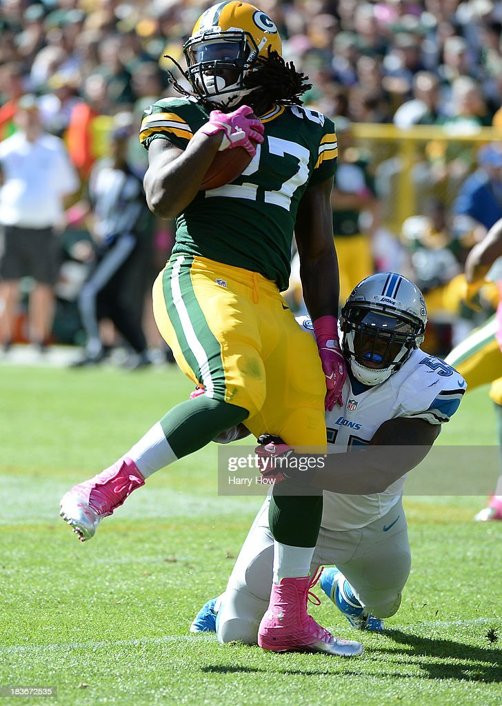 Eddie Lacy #27 of the Green Bay Packers is tackled by Stephen Tulloch #55 of the Detroit Lions as he spins at Lambeau Field on October 6, 2013 in Green Bay, Wisconsin.