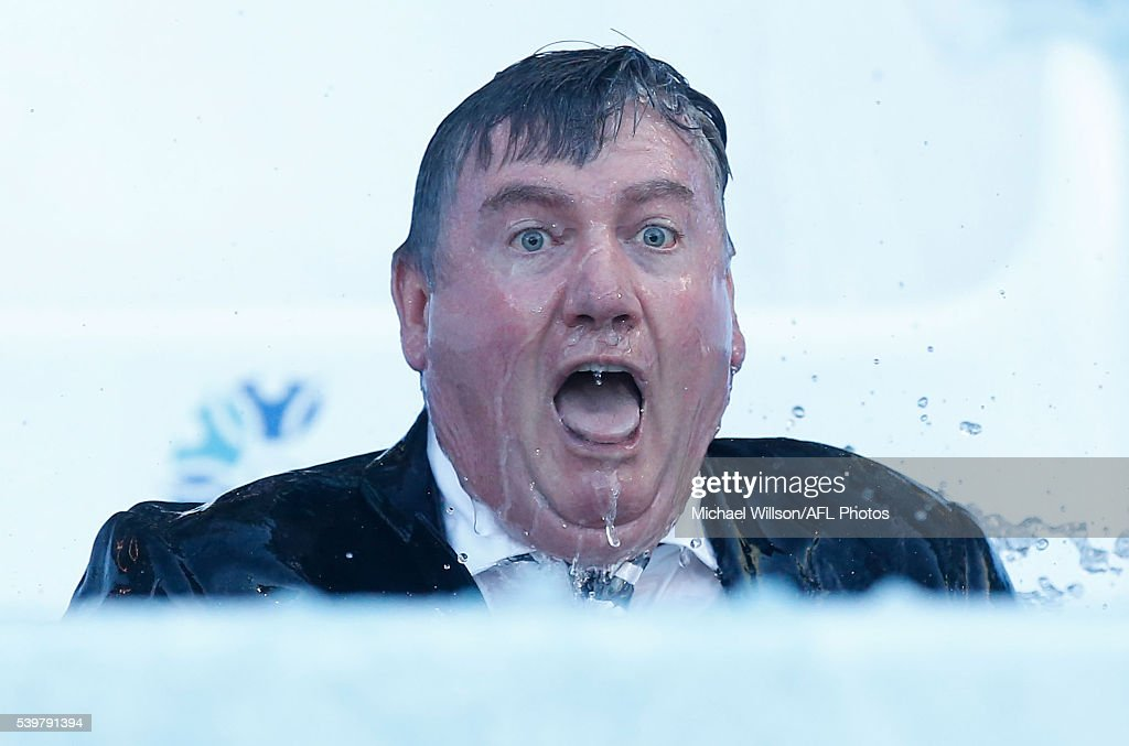 Eddie McGuire emerges from the water after going down the Freeze MND slide during the 2016 AFL Round 12 match between the Melbourne Demons and the...