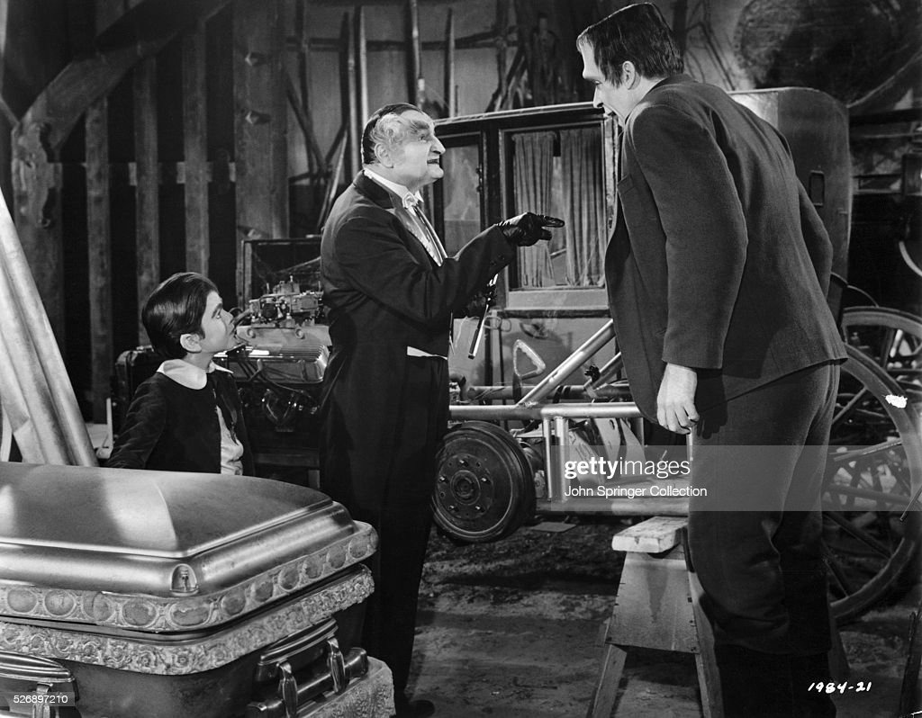 Eddie Munster (Butch Patrick) listens to Grandpa (Al Lewis), as he talks with Herman Munster (Fred Gwynne) in Munster Go Home.