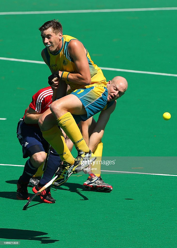 Eddie Ockenden of the Kookaburras jumps clear of a shot on goal by Rob Hammond in the gold medal match between the Australian Kookaburras and England during day four of the 2012 International Super Series at Perth Hockey Stadium on November 25, 2012 in Perth, Australia.