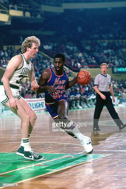 Eddie Phillips of the New Jersey Nets drives to the basket against Larry Bird of the Boston Celtics during a game played in 1983 at the Boston Garden...