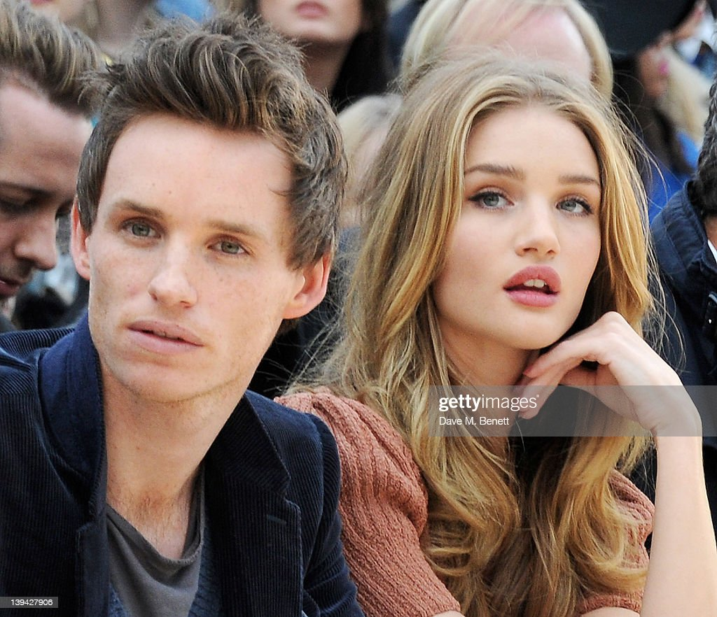 Eddie Redmayne (L) and Rosie Huntington-Whiteley attend the Burberry Autumn Winter 2012 Womenswear Front Row during London Fashion Week at Kensington Gardens on February 20, 2012 in London, England.
