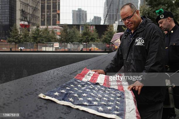 Eddie Reyes places an American flag on the names of fifteen of his colleagues in the New York Police Department Emergency Service Unit who were...