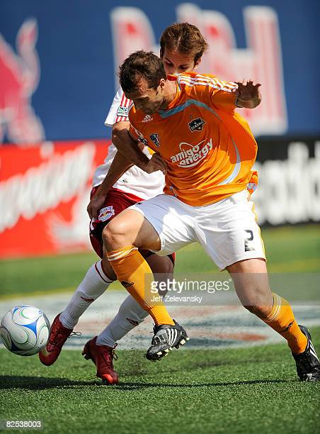 Eddie Robinson of the Houston Dynamo battles for the ball against Mike Magee of the New York Red Bulls at Giants Stadium in the Meadowlands on August...