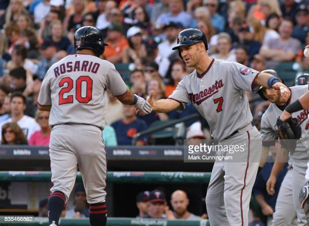 Eddie Rosario and Joe Mauer of the Minnesota Twins shake hands during the game against the Detroit Tigers at Comerica Park on August 12 2017 in...