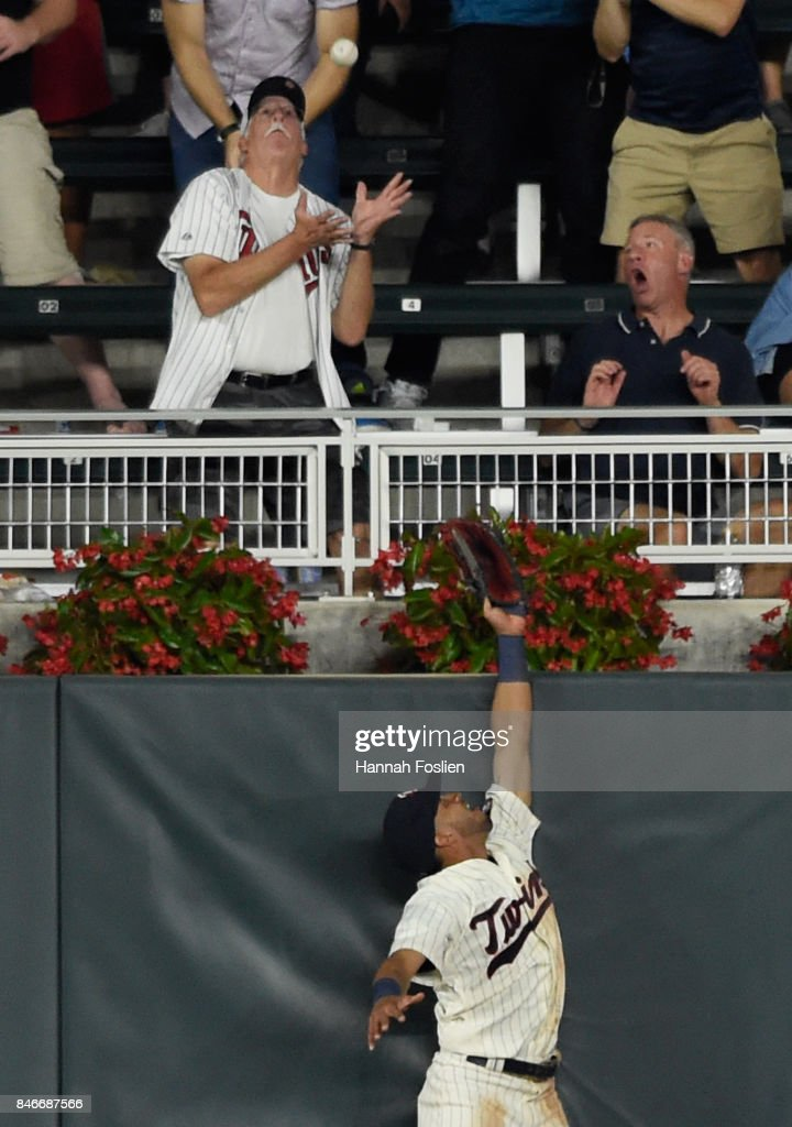 Eddie Rosario #20 of the Minnesota Twins jumps as a fan looks to catch a home run by Austin Hedges #18 of the San Diego Padres during the eighth inning of the game on September 13, 2017 at Target Field in Minneapolis, Minnesota. The Twins defeated the Padres 3-1 in ten innings.