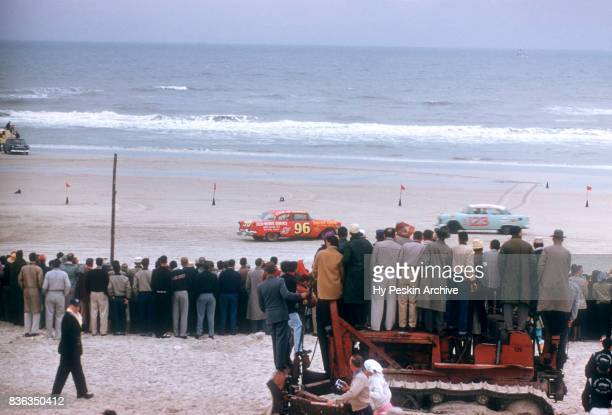 Eddie Skinner in the Oldsmobile and Charles Oldham in the Chevrolet car race along the beach during the Daytona Beach and Road Course on February 26...