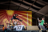 Eddie Vedder of Pearl Jam leaps off the drum kit while Chad Smith of Red Hot Chili Pepper plays drums Matt Cameron plays guitar at Fair Grounds Race...
