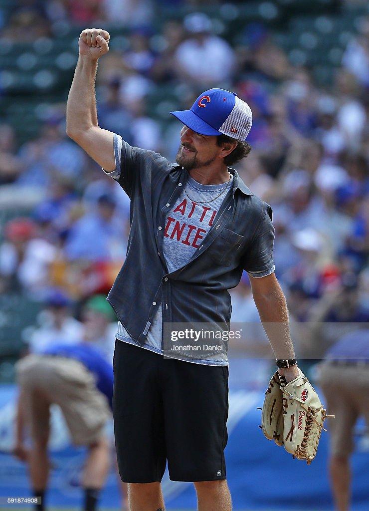 Eddie Vedder of the band 'Pearl Jam' waves to the crowd before throwing a ceremonial first pitch before the Chicago Cubs take on the Milwaukee Brewers at Wrigley Field on August 18, 2016 in Chicago, Illinois.