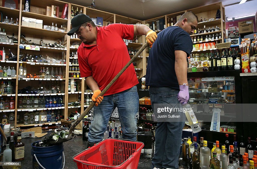 Eddie Villa (L) and Jesus Villa (R) clean up wine bottles that were thrown from the shelves at Van's Liquors following a reported 6.0 earthquake on August 24, 2014 in Napa, California. A 6.0 earthquake rocked the San Francisco Bay Area shortly after 3:00 am on Sunday morning causing damage to buildings and sending at least 70 people to a hospital with non-life threatening injuries.