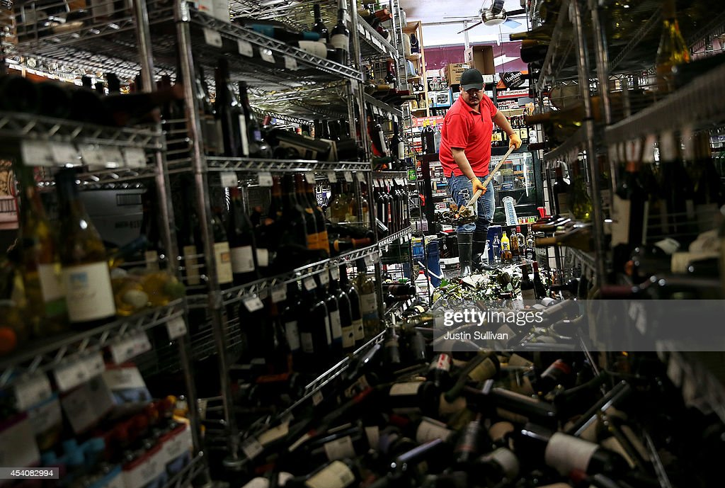 Eddie Villa uses a shovel to clean up wine bottles that were thrown from the shelves at Van's Liquors following a reported 60 earthquake on August 24...