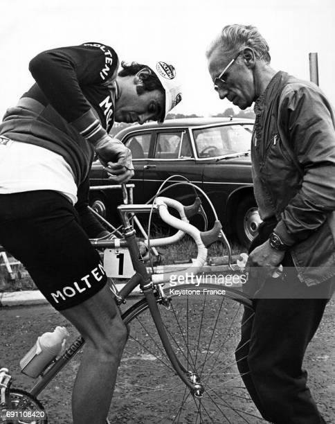 Eddy Merckx sur son vélo répare son guidon