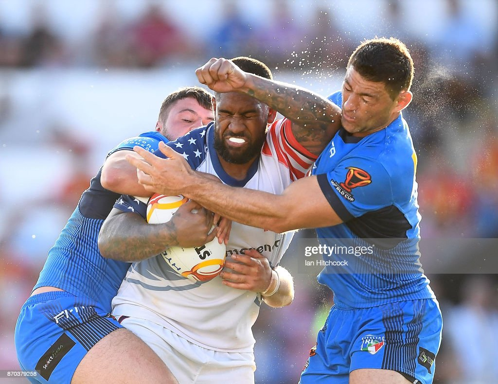 Eddy Pettybourne of the USA is tackled by Mark Minichiello and Nathan Milone of Italy during the 2017 Rugby League World Cup match between Italy and the USA at 1300SMILES Stadium on November 5, 2017 in Townsville, Australia.