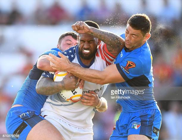 Eddy Pettybourne of the USA is tackled by Mark Minichiello and Nathan Milone of Italy during the 2017 Rugby League World Cup match between Italy and...