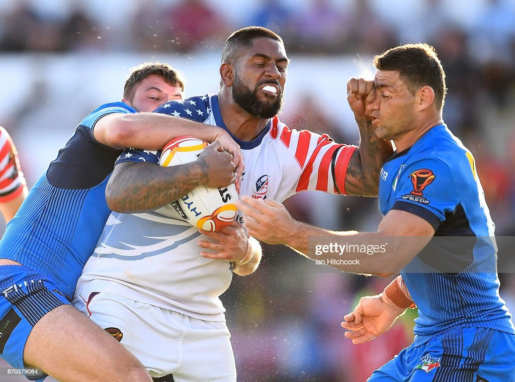 Eddy Pettybourne of the USA is tackled by Mark Minichiello of Italy during the 2017 Rugby League World Cup match between Italy and the USA at 1300SMILES Stadium on November 5, 2017 in Townsville, Australia.