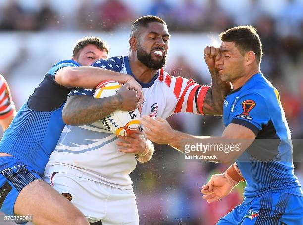 Eddy Pettybourne of the USA is tackled by Mark Minichiello of Italy during the 2017 Rugby League World Cup match between Italy and the USA at...