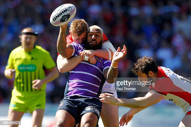 Eddy Pettybourne of Wigan is tackled by Greg Richards and Paul Wellens of during the Super League match between St Helens and Wigan Warriors at...