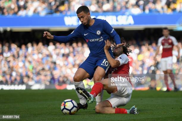 Eden Hazard of Chelsea and Mohamed Elneny of Arsenal battle for possession during the Premier League match between Chelsea and Arsenal at Stamford...