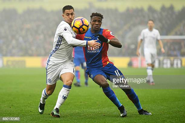 Eden Hazard of Chelsea and Wilfried Zaha of Crystal Palace battle for possession during the Premier League match between Crystal Palace and Chelsea...