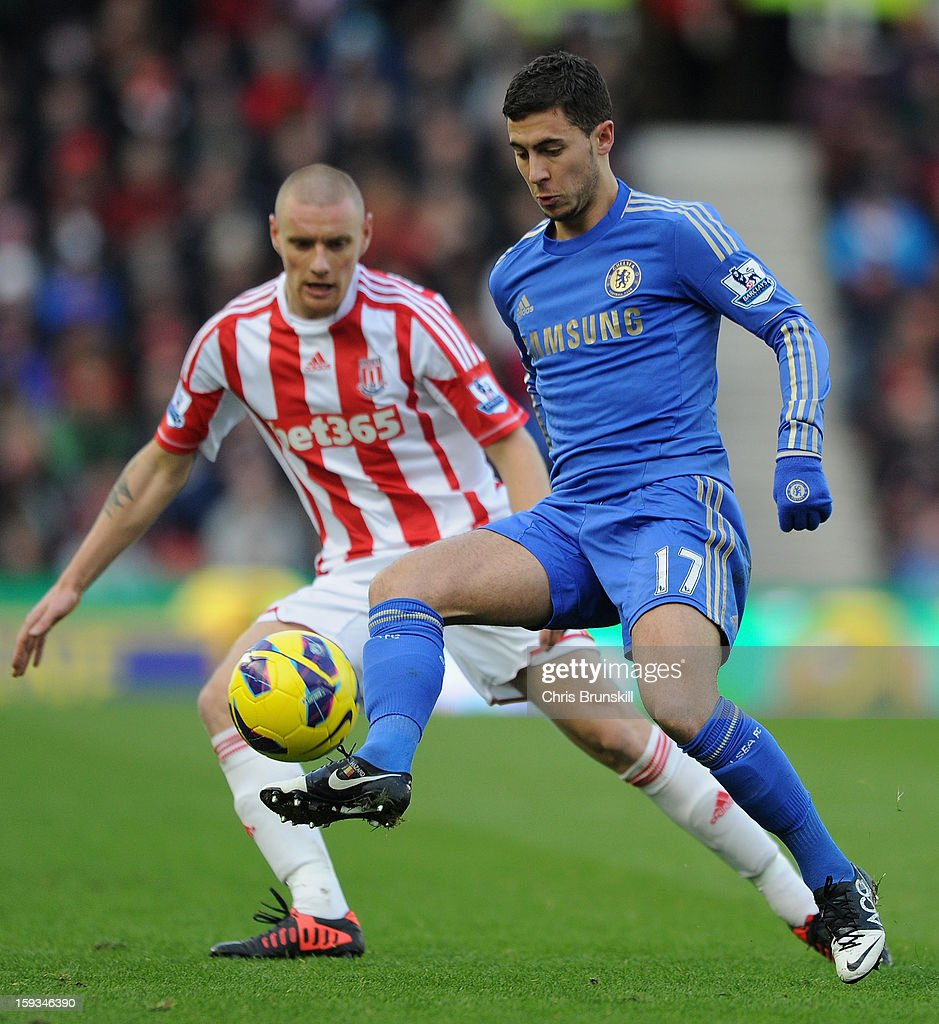 Eden Hazard of Chelsea beats Andy Wilkinson of Stoke City to the ball during the Barclays Premier League match between Stoke City and Chelsea at the Britannia Stadium on January 12, 2013, in Stoke-on-Trent, England.