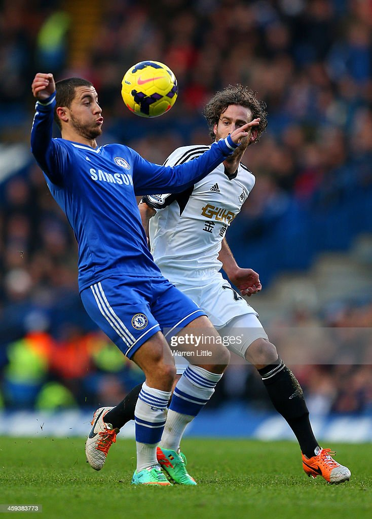 Eden Hazard of Chelsea controls the ball under pressure from Jose Alberto Canas of Swansea City during the Barclays Premier League match between Chelsea and Swansea City at Stamford Bridge on December 26, 2013 in London, England.